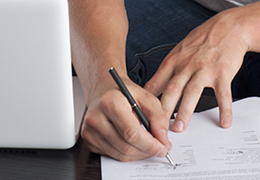 A person is completing the tax form with a pen