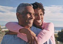 Mature African American couple smiling and hugging outside